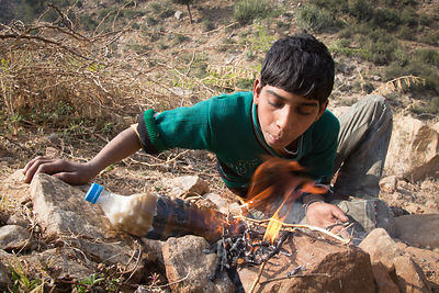 Boys herding goats make chai tea by filling a plastic water bottle with water from a creek, milk from their goat, and tea from their pocket, then boling it over a fire. Bedhnath temple area, Rajasthan, India.