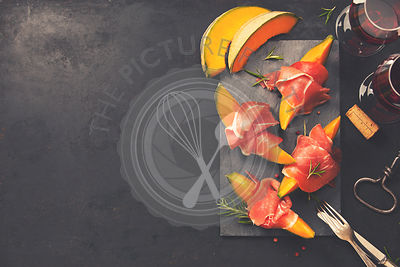 Prosciutto ham with cantaloupe melon, basil leaves and wine over dark grunge background. Top view, copy space