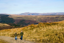 Middle aged couple walking Bwlch y Clawdd above the Rhondda Valley, South Wales, UK.