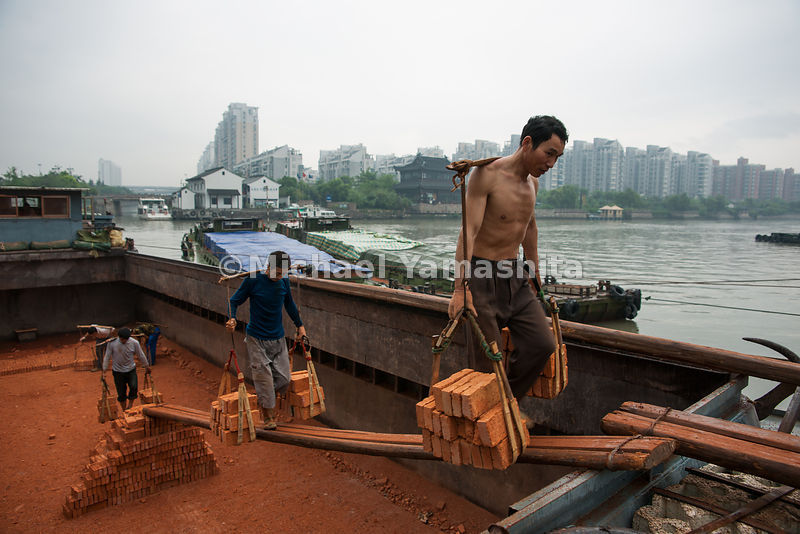 The load of bricks that each stickman carries weighs about 200 pounds. The porters, at Beixinqiao dock in Hangzhou, get the nickname from the handmade bamboo poles they sling across their backs to haul goods. Muscle power has been replaced by cranes and trucks along much of the canal.