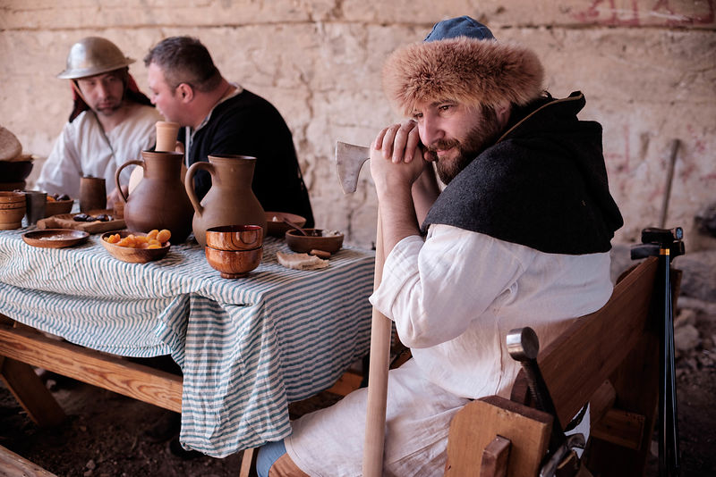 History enthusiasts dressed in costumes sit next to a table during an event to relive the experiences of pilgrims who travelled to Jerusalem during medieval times, March 11, 2016.