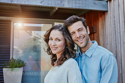 Couple standing in front of door of their home