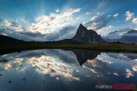 Mountain peak and clouds reflected in alpine lake in the Dolomites