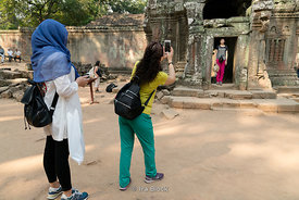 Tourists pose for pictures at Ta Prohm Temple in Siem Reap, Cambodia.