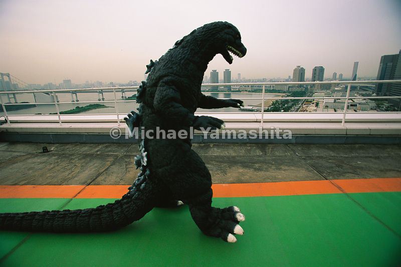 Monstrous sprwal makes for a smoggy backdrop behind costume-clad actor Kenpachiro Satsuma who once played the movie menace Godzilla.