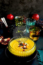 Wine Roasted Vegetable Bisque served with bread and wine. Photographed on a dark blue background.
