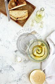 Roasted Padron Pepper Pesto served with white wine and sourdough bread. Photographed on a mixed grey plaster background.