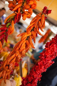 Strings of chilli peppers on a market stall