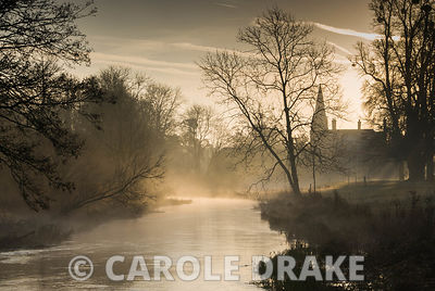 Early morning sun illuminates mist rising from the River Lambourn as it runs through Welford Park, Welford, Newbury, Berkshire, UK. The tower of St Gregory's church is silhouetted in the distance and tall lime trees on the riverbank are garlanded with spheres of mistletoe
