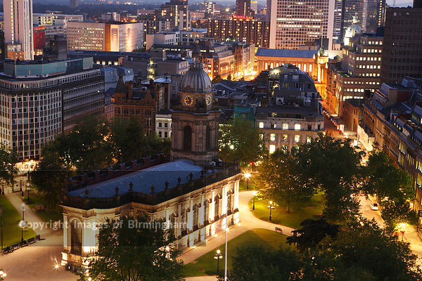 St. Philips Cathedral in the centre of  Birmingham, UK.  Office buildings in the city.  Aerial at night.