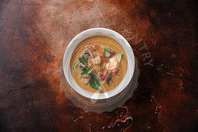 Tom Yam kung Spicy Thai soup with shrimp, seafood, coconut milk and chili pepper in bowl