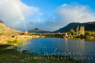 Rainbow over the dam and cottage at Kromrivier farm, Cederberg