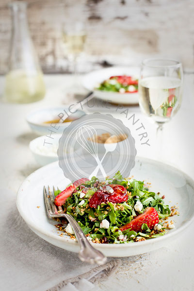 Strawberry Arugula Salad with Hibiscus Vinaigrette served with white wine. Photographed on a white plaster background.