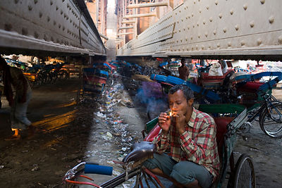 India - New Delhi - A homeless cycle rickshaw driver smokes underneath a bridge at a parking lot next to the Yamuna River where he sleeps