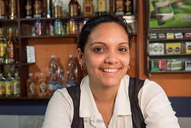 A female bartender at a bar counter in Cienfuegos, Cuba.
