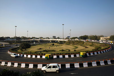 India - New Delhi - Boys play cricket on a gardened Traffic Island