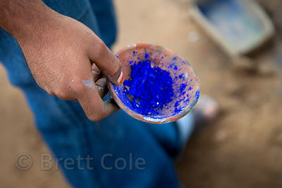 Blue powder being mixed to paint a mural in Pushkar, Rajasthan, India
