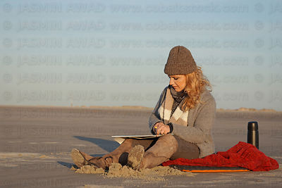 Female artist painting with oil crayons at the beach on a cold day Evening light