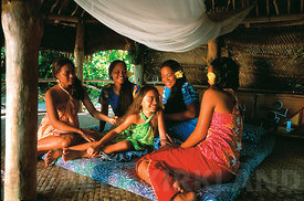 Woman relaxing in a fale, Upolu Island