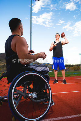 Athletic guy in wheelchair playing football with a friend on an accessible outdoor track