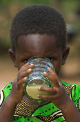Young African drinking goats milk from glass, eastern Uganda, Africa
