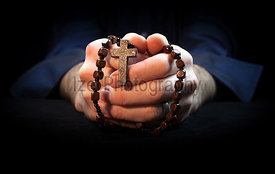 Hands holding rosary beads and cross while praying.