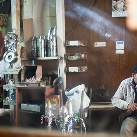 A man reflected in a mirror, smokes inside the Gold Star cafe, Cairo