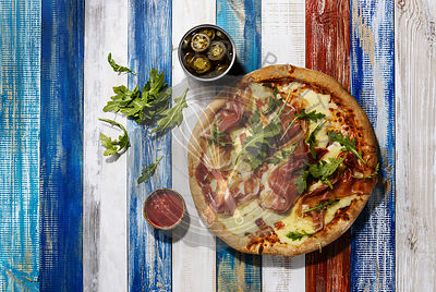Pizza with mozzarella cheese, prosciutto, spicy pepper and arugula leaves on wooden table background