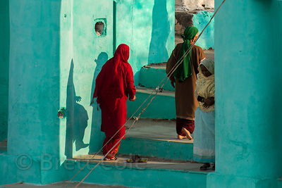 Muslim visitors to Taragarh Fort cast shadows on a teal wall, a common color in Islam, Ajmer, Rajasthan, India