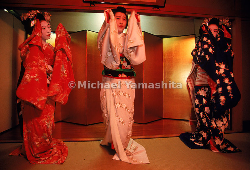 Three geisha in exquisite kimono dance at a party in Kyoto's Gion entertainment district.