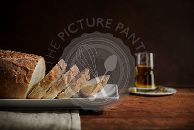 Loaf of rustic, white bread sliced on a plate with oil and herbs nearby on a rich, wood surface.