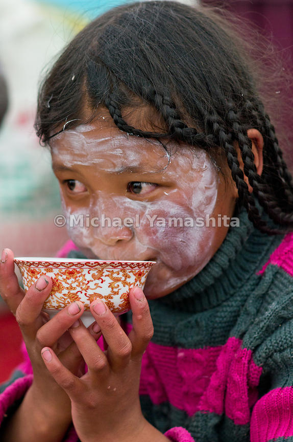 Tibetans are never without their tea and drink an average of 40 cups a day. Ten-year-old Tsering Dolna, slathered a lotion to protect against the intense sun, sips her butter tea, adding precious calories to her diet.