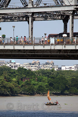 A primitive sailboat passes under Howrah Bridge in Kolkata, India. It's one of the busiest bridges in the world.