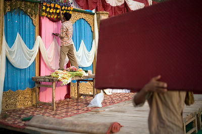 India - Delhi - Workers prepare the stage for a wedding and a florist creates a floral decoration on a canopy above which the bride and groom will sit