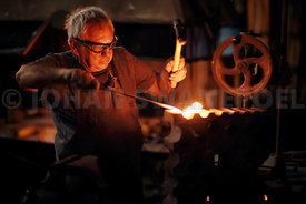 Blacksmith hammering red hot iron