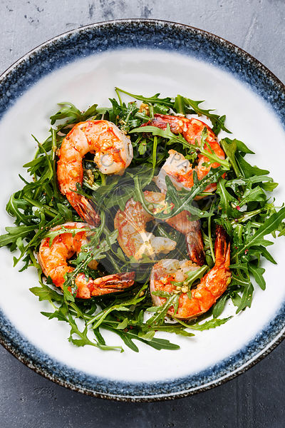 Arugula salad with prawn shrimp close-up