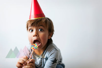 Portrait of little boy with lollipop and red party hat pulling funny faces