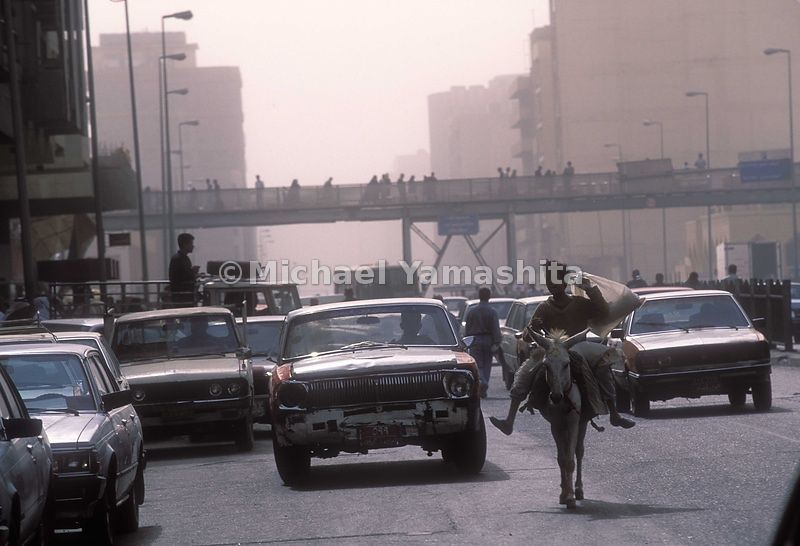 A busy road, full of cars and different means of transportation. Baghdad, Iraq.