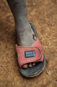 Kenyan child wearing a sandal which is much to large for him.