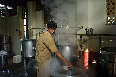 India - Kozhikode - A kitchen hand works through the steam in the kitchens of the Medical College brach of the Indian Coffee House