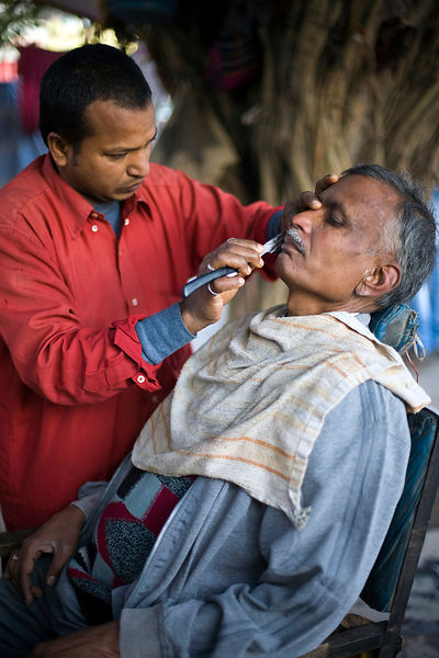 India - Delhi - Ranjit Sharma, 59 has his haircut by a roadside barber outside the Fatepuri night shelter for the homeless before going to work.