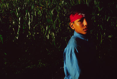 A boy with a Maoist headband in his field, Dolakha, Nepal