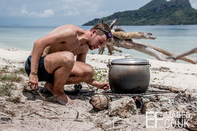 Man Cooking Lunch Over A Fire On The Beach