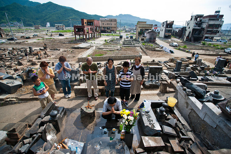 Families gather to clean grave sites and honor their ancestors. See April pics taken from this cemetery buried by tsunami debris with soldiers searching for bodies. Broken headstones caused by fires and explosions of propane tanks from Koganji Temple buildings