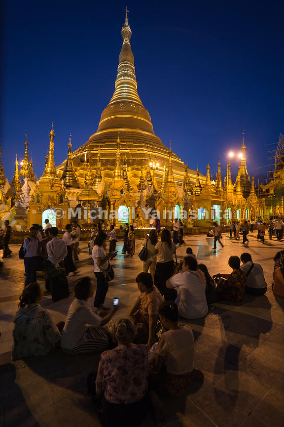 Locals gather on the main concourse of Shwedagon Pagoda after nightfall. The pagoda is considered Myanmar's greatest treasure, a massive gold-plated wonder that embodies the country's natural and spiritual bounty. Its 99-meter (325-foot) spire looms magnificently over the city's skyline and radiates golden light in all directions.