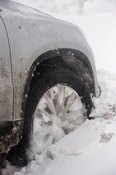 Close up of car wheels stuck in snow drift.