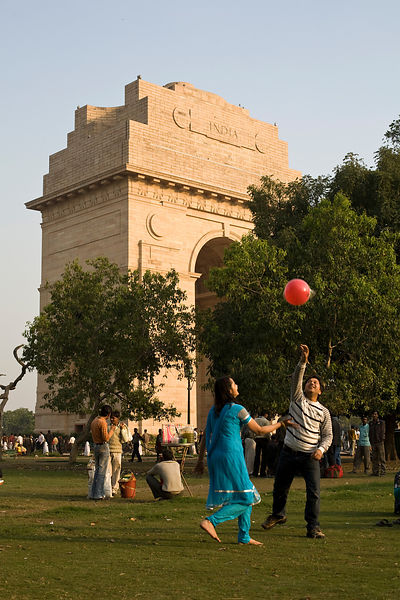 India - Delhi - A couple play with a red balloon by India Gate