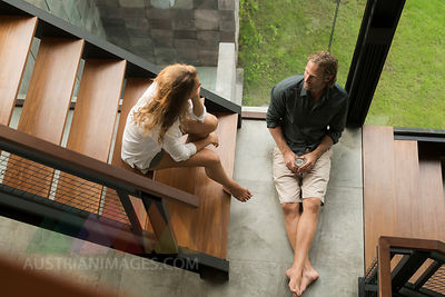Top view of couple having a talk on stairs in modern design house