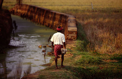 India - Kerala - A man walks past a river in the Backwaters