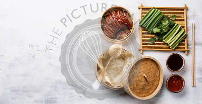 Sliced Peking Duck in bamboo steamer served with fresh cucumber, green onions, cilantro and roasted wheaten chinese pancakes with sauce Hoysin on white background copy space